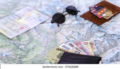 Higher contrast composition on travel topic.  Unfolded detailed topographic map exotic Asian cash notes credit cards sunglasses passport entry stamps many