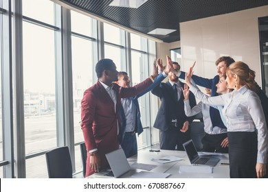 High-five! cheerful young business people giving high-five while their colleagues looking at them and smiling