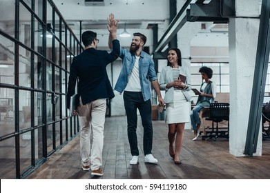 High-five!  Full length of two cheerful young business people giving high-five while their colleague looking at them and smiling