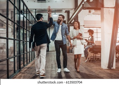 High-five!  Full length of two cheerful young business people giving high-five while their colleague looking at them and smiling - Shutterstock ID 613503704