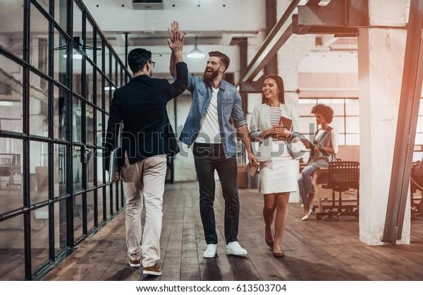 Hoch fünf!  Vollständige Länge von zwei fröhlichen jungen Geschäftsleuten, die fünf hoch geben, während ihr Kollege sie anschaut und lächelt