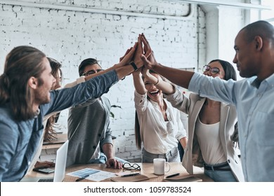 High-five for success! Diverse group of business colleagues giving each other high-five in a symbol of unity and smiling while working in the board room