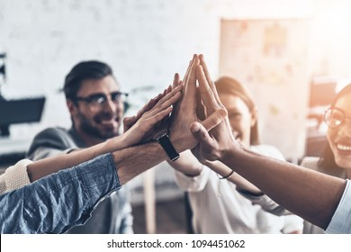 High-five! Top view of business colleagues giving each other high-five in a symbol of unity and smiling while working in the board room