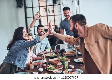 High-five! Young man and woman giving each other high-five while enjoying dinner party among friends