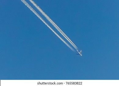 High-flying passenger aircraft with chemtrails in the sky. The airplane is a commercial airliner.