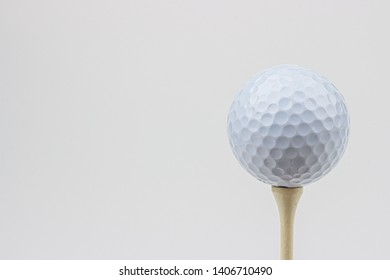 A high-key photo of a white golf ball on a golf tee.