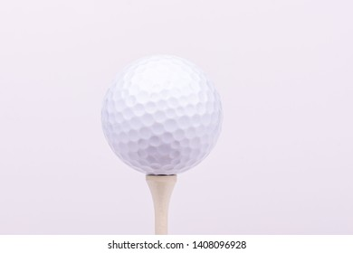 A high-key portrait of a golf ball on a golf tee.