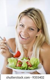 high-key portrait smiling female eating her salad