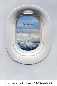 Highland landscape with airplane above the mountainous peaks in winter - view on a snow hills through the plane porthole window. Vertical billboard or poster for your concept of passenger air travels.