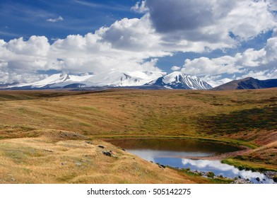 Highland little round lake on the background of high snow mountain peaks under the blue sky and white clouds, Plateau Ukok Altai mountains Siberia Russia