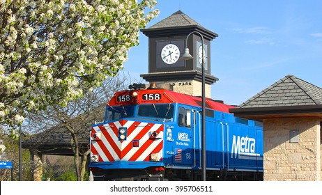 Highland Park, IL, USA - May 7, 2015: A springtime late afternoon view of a Metra commuter train leaving the Highland Park station, with a clock tower and spring white tree blossoms.
