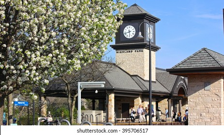 Highland Park, IL, USA - May 7, 2015: A springtime late afternoon view of  the Metra station in Highland Park, with commuters after the train had left, a clock tower and spring white tree blossoms.