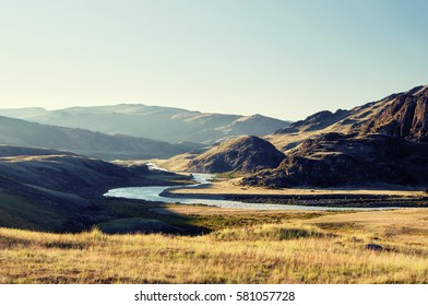 Highland river valley with yellow grass on a background of snow covered mountains and glaciers under clouds and blue sky, Plateau Ukok, Altai mountains, Siberia, Russia