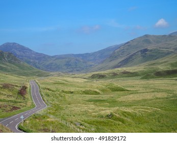 HIGHLANDS, empty country road across scottish moorland in desolate glen (valley) in mountains landscape and clear blue sky in warm sunny summer day: SCOTLAND / GREAT BRITAIN UK / EUROPE – AUGUST 2016.