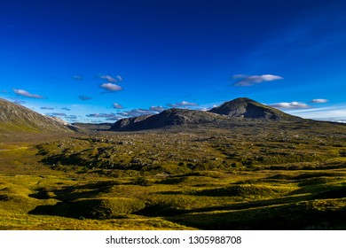 Highlands With Mountains And Spectacular Sunlit Valley near Durness And Rhiconich In Scotland