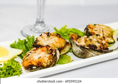 A highlighted Clams Casino appetizer plate with the stem of a wine glass in the background