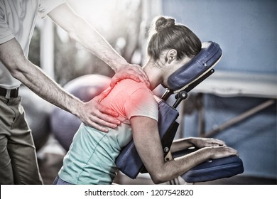 Highlighted pain against physiotherapist giving back massage to a female patient