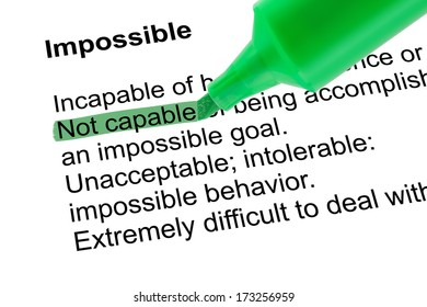 Highlighted word Not capable for Impossible with green pen over white paper. Isolated white background.