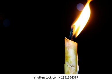 Highlighting the flame of a burning cande, with a dark background focusing the high burning flame and the melting wax