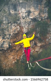 Highline in the fog. Highliner on the background of the rock. A woman catches the balance on a stretched sling. Rope walker in the haze.