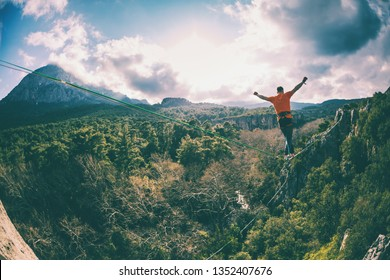 Highline in the mountains. A man walks along a stretched sling against a cloudy sky. Highline is on the line. Ropewalker catches the balance. Equilibrium.