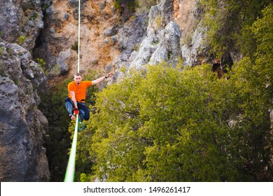 Highline on the background of the mountains. A man sits on a stretched sling. Performance of a tightrope walker. Highliner balances over the abyss. The athlete is trying to get up after a fall.