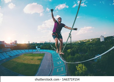 Highliner goes over the stadium. A man walks along a stretched sling over the city. Ropewalker catches the balance. The development of a sense of balance. Highline in the city.