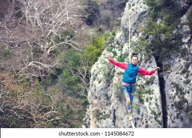 Highliner on a rope. Highline on a background of mountains. Extreme sport on the nature. Balancing on the sling. Equilibrium at altitude. A woman catches balance on the line.