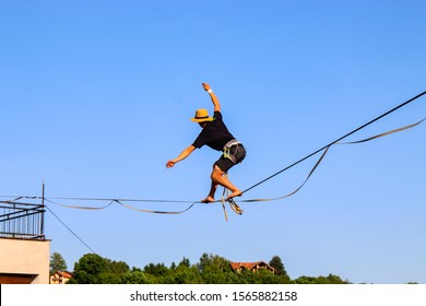 Highliner on a rope. Highline on a background of blue sky. Extreme sport on the nature. Balancing on the sling. Equilibrium at altitude.