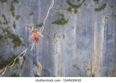 Highliner sits on a sling. The athlete is trying to get up. A man catches a balance on a stretched rope. Highline in the mountains.
