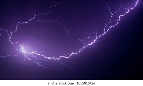 Highly branched lightening (lightning) taking an almost spiral path seen against a deep purple stormy night sky. Sometimes described as anvil or spider crawler lightening.