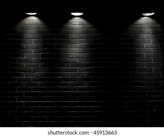 Highly contrasted spotlights on an outdoor black brick wall