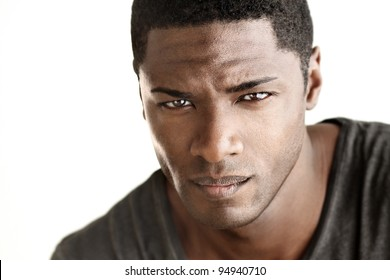 Highly detail portrait of young good looking man staring at viewer against white neutral background