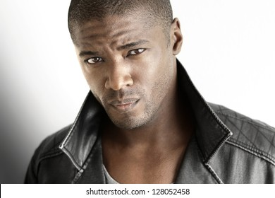 Highly detailed closeup portrait of a tough looking stylish man against white background