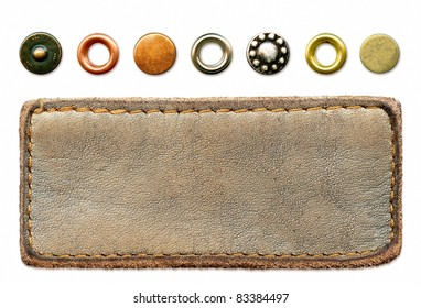 Highly detailed grungy blank natural leather jeans label with set of worn metal rivets, isolated on white background