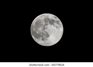 Highly detailed photo of the bright full moon in the night sky as seen through an astronomy telescope