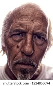 Highly detailed portrait of older white man with gray hair and goatee, back lit, not isolated, looking directly at viewer. Shallow depth of field, focus on bridge of nose, eyes a little soft at 100%