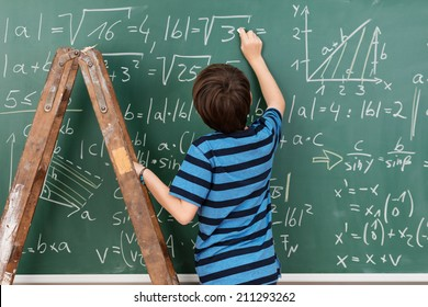 Highly intelligent little boy in the classroom standing on a stepladder to reach a complex mathematical problem on the blackboard that he is busy solving