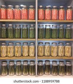 A highly organized pantry stocked with shelves of uniformly spaced mason jars filled with canned preserved food and vegetables.