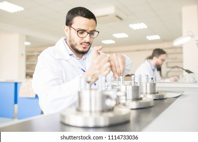 Highly professional bearded technician wearing lab coat repairing pressure transducers while sitting at desk of spacious measuring equipment factory, portrait shot