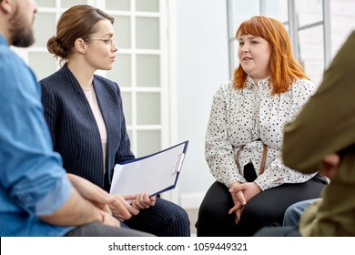 Highly professional young psychologist listening to her obese patient suffering from eating disorder with concentration while conducting group therapy session at cozy office