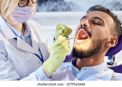 Highly professional young stomatologist wearing medical mask and white coat using dental mirror while examining mouth cavity of handsome patient, close-up shot