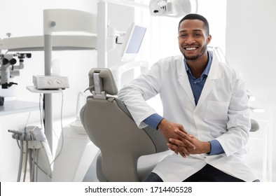 Highly qualified young black dentist posing at clinic over modern cabinet, empty space