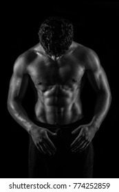 Highly retouched black and white fitness model and bodybuilder. Looking to himself. Posing abs and chest. Concept of power, energy and confidence. black background.