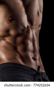 Highly retouched chest muscles and six pack abs. Concept of power and healthcare. black background.