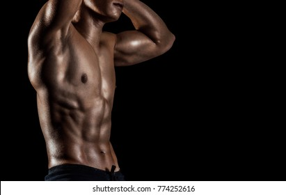 Highly retouched fitness model and bodybuilder. Posing chest and six pack abs. Concept of power and healthcare. black background.