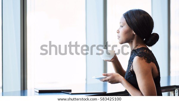 Highly successful young African American woman looking out the window while drinking her morning coffee, while reflecting on her past and thinking about her future.
