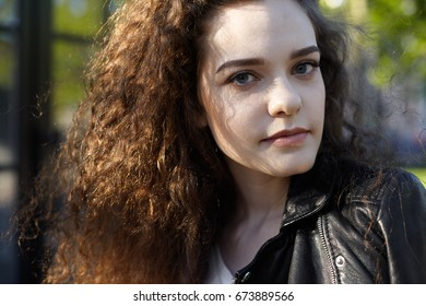 Highly-detailed close up portrait of beautiful young woman with clean healthy skin and long curly dark hair relaxing outdoors on sunny day. People, leisure and modern urban lifestyle concept