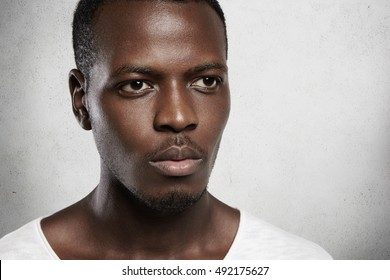 Highly-detailed close up shot of African man looking serious and confident, standing isolated against white wall background. Thoughtful and peaceful facial expression, relaxed and regular mimics
