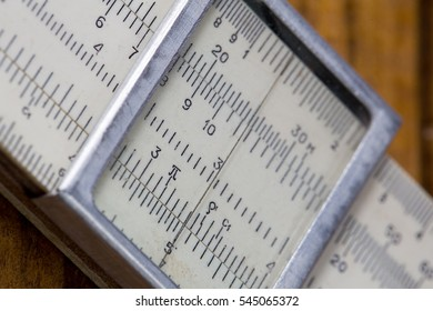 high-precision hand-held calculating tools - logarithmic ruler  brown wooden background